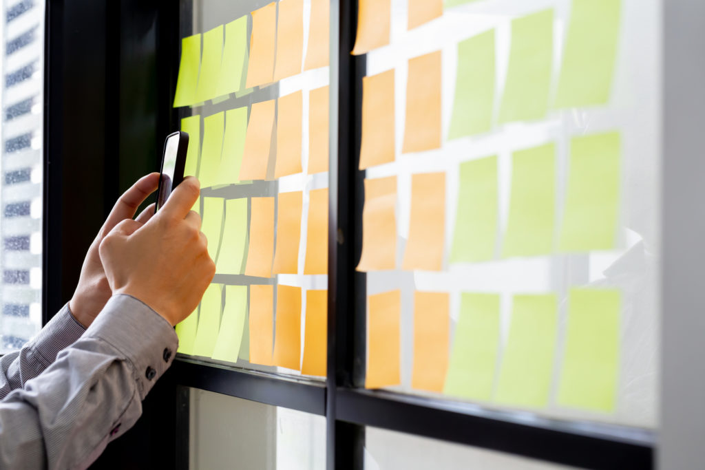 IT worker tracking his tasks on kanban board in mobile phone application. Using task control of agile development methodology. Man attaching sticky note to scrum task board in the office